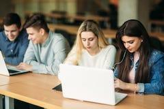 Il gruppo di studenti di college che studiano nella biblioteca di scuola, una ragazza e un ragazzo stanno utilizzando un computer Immagine Stock Libera da Diritti
