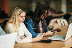 Il gruppo di studenti di college che studiano nella biblioteca di scuola, una ragazza e un ragazzo stanno utilizzando un computer Immagine Stock