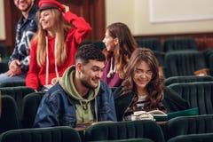 Il gruppo di studenti felici allegri che si siedono in un corridoio di conferenza prima della lezione immagini stock libere da diritti