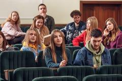 Il gruppo di studenti felici allegri che si siedono in un corridoio di conferenza prima della lezione fotografia stock libera da diritti