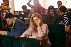 Il gruppo di studenti felici allegri che si siedono in un corridoio di conferenza prima della lezione fotografia stock