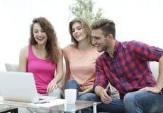 Il gruppo di studenti guarda il video sul computer portatile Fotografia Stock