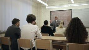 Il gruppo di studenti in un'aula, ascoltante come loro insegnante tiene una conferenza archivi video