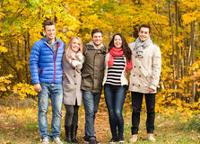 Il gruppo di uomini sorridenti e le donne in autunno parcheggiano Immagini Stock