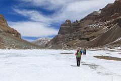 Il gruppo di viaggiatori con zaino e sacco a pelo sta camminando sul fiume congelato sul modo alla montagna di Kailash, Tibet Fotografia Stock