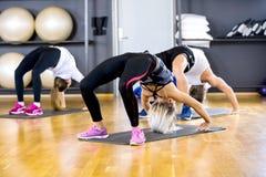 Il gruppo di yoga sta in ponte alla palestra di forma fisica Fotografia Stock