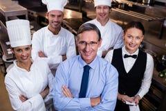 Il gruppo felice del ristorante che sta insieme alle armi ha attraversato in cucina commerciale fotografia stock