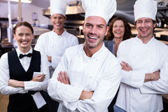 Il gruppo felice del ristorante che sta insieme alle armi ha attraversato in cucina commerciale fotografia stock libera da diritti
