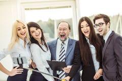 Il gruppo felice di affari fa un selfie che sta vicino alla finestra nell'ufficio Fotografia Stock