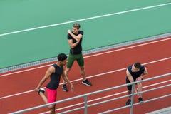 Il gruppo multietnico concentrato dell'atleta fa l'allungamento degli esercizi Fotografie Stock Libere da Diritti