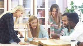 Il gruppo razza mista di studenti universitari che fanno linguistico ricerca, girando le pagine di grande vecchio riferimento stock footage