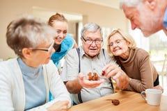 Il gruppo senior gioca con un puzzle immagine stock