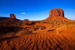 Il guanto e Merrick Butte ad ovest della valle del monumento abbandonano le dune di sabbia Immagine Stock