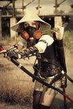 Il guerriero attraente della donna nella tenuta della maschera in sue mani piega immagini stock libere da diritti
