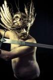 Il guerriero con il casco e la spada con il suo corpo hanno dipinto la polvere di oro Immagine Stock