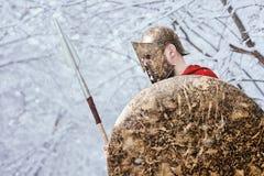 Il guerriero spartano solo tiene la sua armatura nella foresta Immagine Stock