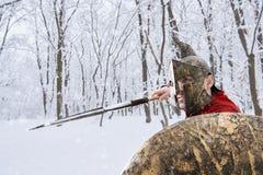 Il guerriero spartano sta cercando nella foresta dell'inverno Fotografie Stock
