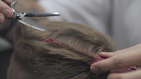 Il hairstyling degli uomini e haircutting nel negozio di barbiere o nel salone di capelli al rallentatore video d archivio