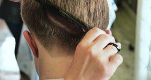 Il hairstyling degli uomini e haircutting in un salone di capelli Pettinando e tagliando capelli barbershop video d archivio