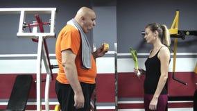 Il hamburher mangiatore di uomini grasso in una palestra ed esamina sarcastico una sportiva stock footage