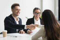 Il handshake sorridente del responsabile di ora ha impiegato il richiedente femminile al lavoro int fotografia stock