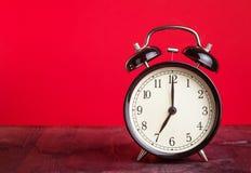 Il horloge de ` du ` s sept o déjà, heure de se réveiller pour l'amour, vieux réveil métallique noir de vintage sur le fond rouge Images stock