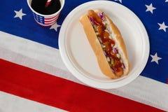 Il hot dog è servito in piatto con una bevanda sulla bandiera americana Fotografia Stock
