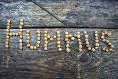 Il hummus di parola dai piselli su una base di legno Fotografia Stock Libera da Diritti