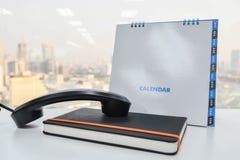 Il IP telefona il microtelefono sul taccuino e sul calendario fotografie stock