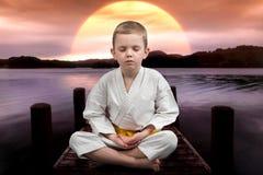 Il karatè del ragazzino medita, si rilassa la seduta sul ponte sul fiume Esercizio all'aperto Il vincitore dell'atleta Fotografia Stock