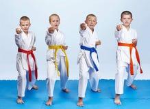 Il karateka quattro in karategi sta battendo il braccio della perforazione fotografia stock