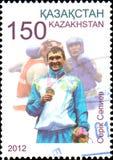 IL KAZAKISTAN - CIRCA 2012: Il francobollo stampato nel Kazakistan mostra il campione olimpico Serik Sapiev Fotografia Stock Libera da Diritti