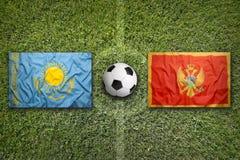 Il Kazakistan contro Bandiere del Montenegro sul campo di calcio Fotografia Stock
