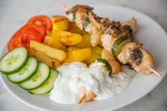 Il kebab del pollo è servito con i potatos, il cetriolo, i pomodori e il tzatziki americani fotografia stock