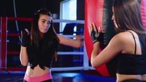 Il kickboxer della ragazza risolve i colpi sulla pera nella palestra