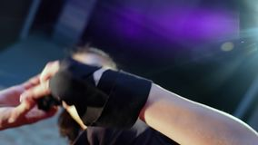 Il kickboxer della ragazza tira le sue fasciature di sport delle mani