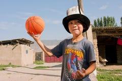 Il KIRGHIZISTAN: Il bambino nel cappello del cittadino gioca la pallacanestro in un villaggio Fotografie Stock Libere da Diritti