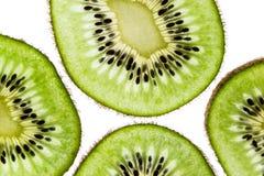 Il kiwi affettato suona sulla macro bianca di vista superiore del fondo immagine stock