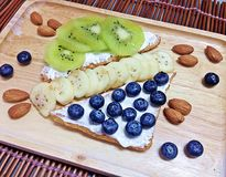 Il kiwi ed i mirtilli spruzzano con le banane e le mandorle immagini stock
