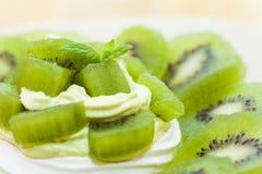 Il kiwi ha montato il dessert del nido della meringa e della crema Immagini Stock