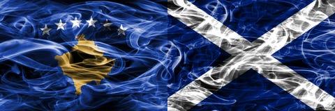 Il Kosovo contro le bandiere del fumo della Scozia disposte parallelamente fotografia stock