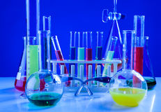 Il laboratorio di chimica differente ha messo su una tavola sopra fondo blu Fotografia Stock