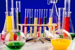 Il laboratorio di chimica differente ha messo su una tavola sopra fondo blu Immagine Stock
