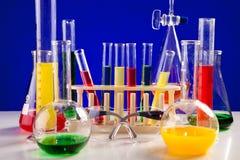 Il laboratorio di chimica differente ha messo su una tavola sopra fondo blu Fotografia Stock Libera da Diritti
