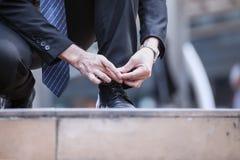 Il laccetto del legame dell'uomo d'affari o allaccia le scarpe nere sul pavimento, fine Immagine Stock Libera da Diritti