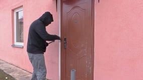Il ladro con la porta aperta del bastone a leva ed ottiene in casa stock footage