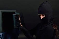 Il ladro della donna si rompe in una cassaforte ed estrae una catena dell'oro Immagine Stock