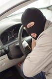 Il ladro nella maschera ruba l'automobile Immagine Stock