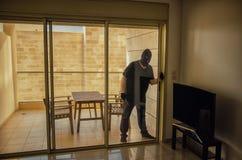 Il ladro in passamontagna entra in appartamento dal balcone fotografie stock libere da diritti