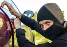 Il ladro rompe il portello nell'automobile Fotografia Stock